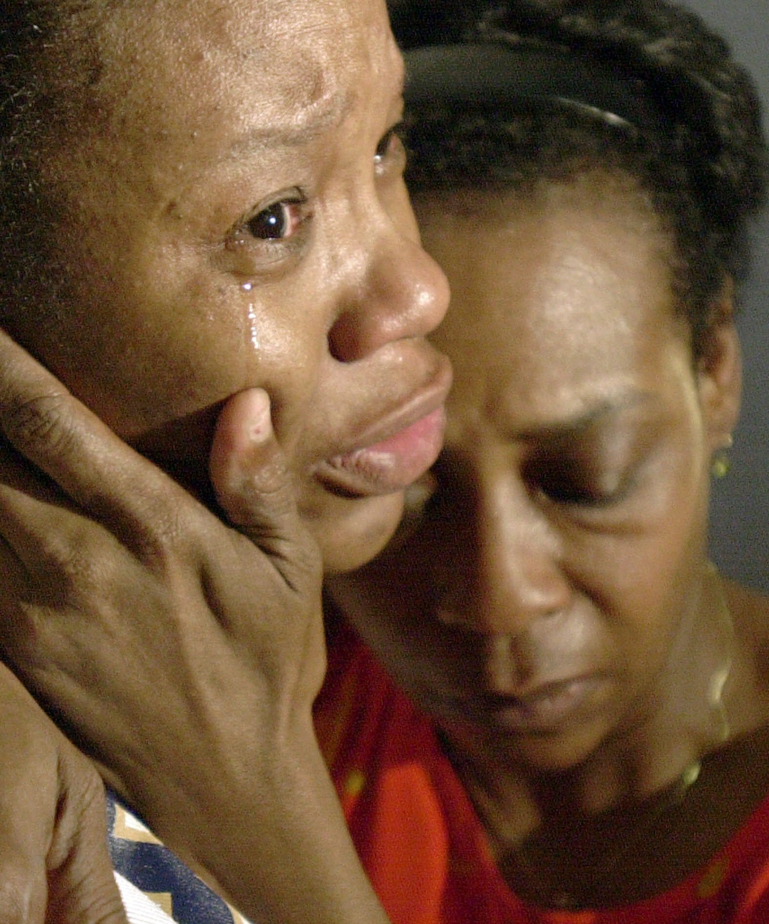 Shelia Smith, left, and Mary Bradley console one another Sunday, July 8, 2001, outside the Chicago apartment of Tracey Bradley, mother of Diamond, 3, and Tionda Bradley, who went missing from their home on the South Side on July 6, 2001.  Smith is Tracey's aunt and Mary Bradley is Tracey's mother and the children's grandmother.