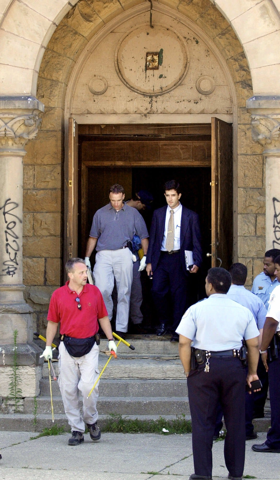 FBI and Chicago Police officials leave an abandoned church Friday, July 13, 2001, after searching the basement for sisters Tionda, 10, and Diamond Bradley, 3, who had been missing for a week. The search turned up nothing.