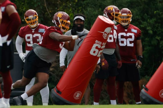 Washington Football Team defensive end James Smith-Williams (96) pushes past blocking dummies during drills as part of minicamp at Inova Sports Performance Center on June 10.