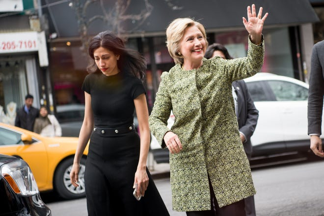Hillary Clinton, right, waves as she arrives to talk with patrons at the Jackson Diner on April 11, 2016 in the Flushing neighborhood of the Queens borough of New York City. Her aide Huma Abedin is by her side, left.