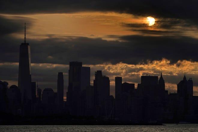 Le soleil est partiellement éclipsé alors qu'il se lève sur le bas Manhattan à New York, le jeudi 10 juin 2021.