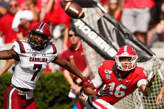 Georgia wide receiver Demetris Robertson (16) tries to pull in a pass from quarterback Jake Fromm (11) while being defended by South Carolina defensive back Jammie Robinson (7) in the first half of a game in Athens on Oct. 12, 2019. [Photo/Joshua L. Jones, Athens Banner-Herald]