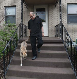 The Rev. Louis Thomas, pastor of St. Andrew the Apostle Catholic Church in Norton, walks out of the rectory with his dog, Roxy, on Friday.