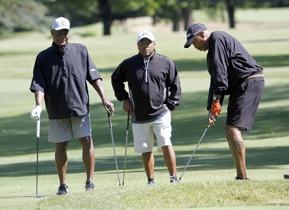 Austin Carr (left) and Jeff Gilbert (middle) watch Tony Roseboro hit a shot at the Wendy's Golf Classic in 2019.