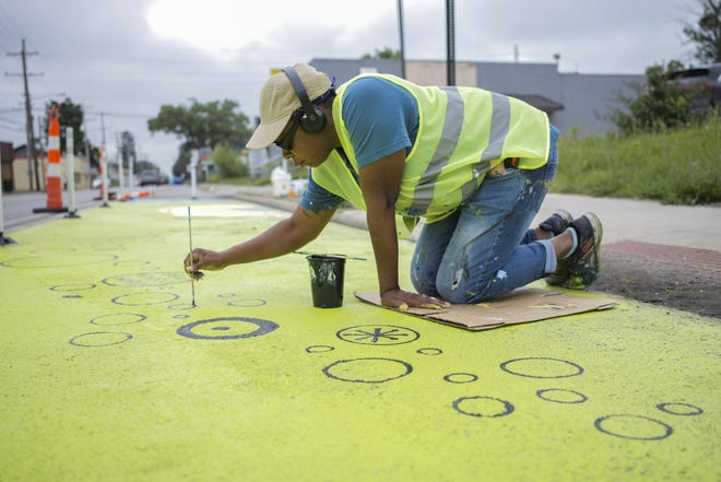 Artist April Sunami paints a mural along Sullivant Avenue Thursday. Working with Designing Local, an urban planning firm, 21 artists created a series of temporary and permanent murals along the road's pavement.