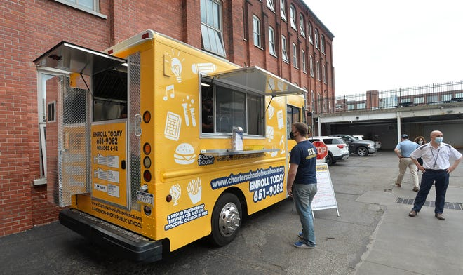 """Staff members of the Charter School of Science order lunch at the school """"Food For Thought"""" food truck in Erie."""
