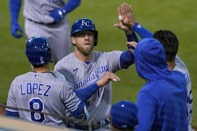 Kansas City Royals' Hunter Dozier, middle, is congratulated by teammates after scoring against the Oakland Athletics during the seventh inning of Thursday's game in Oakland. The Royals snapped a five-game losing streak with a 6-1 win.