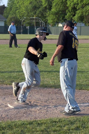 New London's Carter Allen rounds third base with congratulations from Coach Brad Helmerson on a two-run home run against the Falcons Thursday at West Burlington High School.
