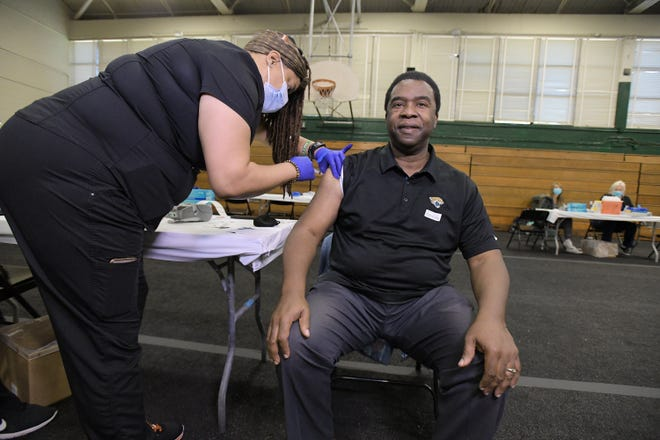 """Former Jacksonville mayor Alvin Brown, shown here getting the COVID-19 vaccine in April, said a renewed campaign using """"trusted voices"""" is needed to convince people they should get the shot. Brown is co-chairman of the Statewide Coronavirus Vaccination, Community Education and Engagement Taskforce."""