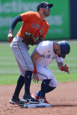 Toronto Blue Jays' Randal Grichuk, right, collides with Houston Astros shortstop Carlos Correa, left, breaking up a potential double play opportunity during the second inning of a game in Buffalo, N.Y. on Sunday, June 6, 2021.