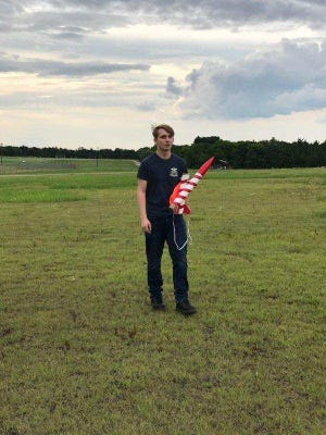 Kelton Kuntz poses with a rocket during launches. Kuntz will be competing in national rocketry challenges this weekend while representing Sherman High School.