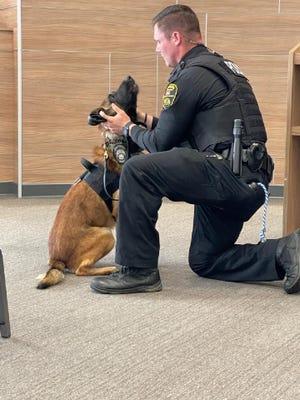 Officer Tyler Buchanan pets newly-badge K-9 unit Echo during a city council meetingm