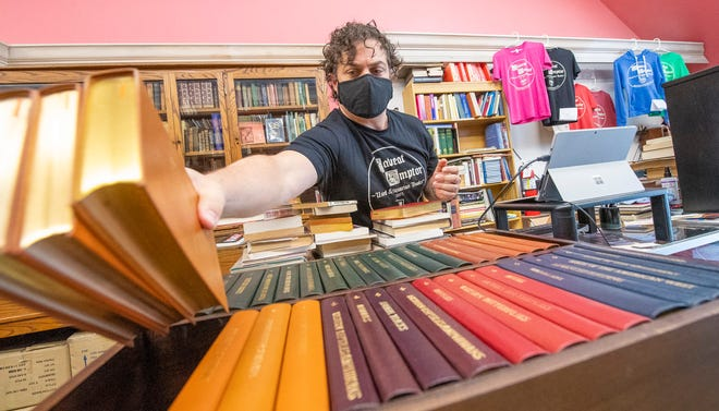 Owner Eric Brown sorts through a recently purchased collection Wednesday at Caveat Emptor, which is celebrating 50 years in business.