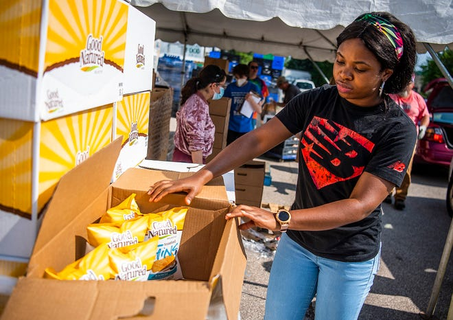 Rebecca Udoekong opens a box of food for distribution during this week's Fresh Friday event at Hoosier Hills Food Bank,  2333 W. Industrial Park Drive.