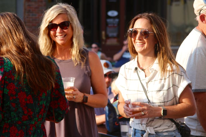 """Stacey Sills, left, and Ginny Ruch share a laugh on Thursday, June 10, during downtown Zeeland's """"Music on Main Street,"""" a kick-off event for the city's social district."""