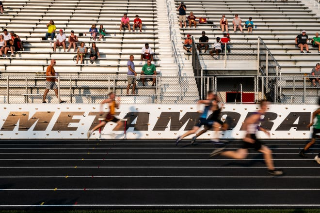 Runners compete in the 100 meter dash during state qualifiers at Metamora Township High School on Thursday, June 10, 2021.