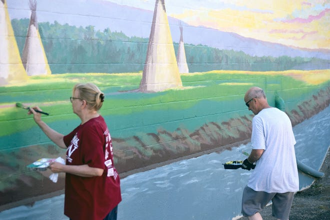 Nancy Bauder and Alan Collins work on a mural Friday at the First City Museum. The artists are painting an American Indian scene on a 57 by 14-foot space of an exterior wall of the downtown museum.