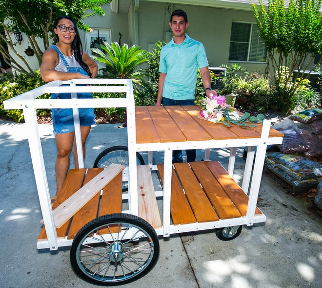 Krista Ingrilli stands by the floral cart that her boyfriend, Delfino Garza, right, is building for her. She is opening Eufloria Flower Cart on June 26 at the Ocala Downtown Market.