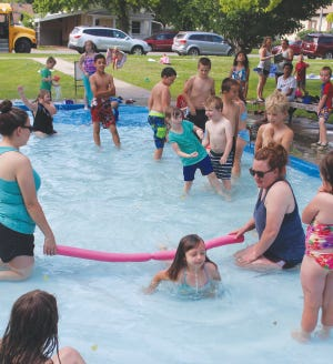 Pratt Rec staff workers Myra Tresner and Katie Ray hold a pool noodle limbo line for children at the Zerger Park wading pool during water fun day activities.