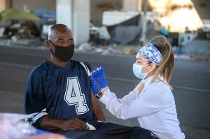 Nurse Bianca DeAquino with the San Joaquin County Clinics, right, gives a shot of the Johnson and Johnson COVID-9 vaccine to Richard Caldwell at an homeless encampment under the I-5 overcrossing at Weber Avenue in downtown Stockton.