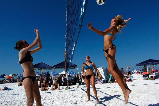From left, Taylor Jais, Savannah Davis and Kristina Pellitteri guard the net during a Dig the Beach volleyball game at Siesta Key Public Beach.