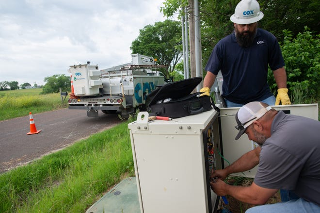 Cox Communication field technicians Lance Doyal, front, and Adam Colgrove test a fiber line that connects internet to rural houses in northern Shawnee County on Friday afternoon. Cox was able to expand its coverage to this area through federal CARES money and is working with local officials to continue expansion of broadband access.