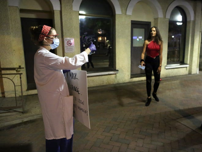 Dr. Madeline Smoot of UF Health gives a thumbs up to a bar patron who took a mask to wear at a bar as a group of doctors and medical students passed out masks and tried to raise awareness about the need to wear masks during a Friday night downtown in late November.