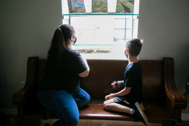 Sara and her son peer out a window at the Community Rescue Mission in Fort Smith.