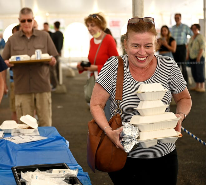 Ruth Jacob carries an armful of Greek food during the Arlington Greek Festival at the St. Athanasius the Great Greek Orthodox Church, June 11, 2021.  The festival continues all day Saturday and Sunday.