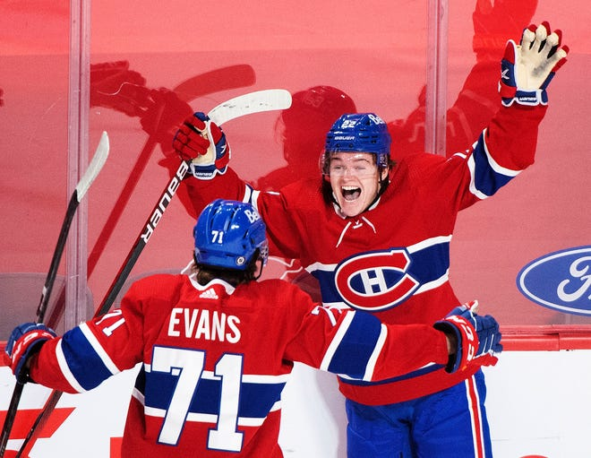 FILE - In this May 1, 2021, file photo, Montreal Canadiens' Cole Caufield (22) celebrates with teammate Jake Evans after scoring against the Ottawa Senators during overtime of an NHL hockey game in Montreal.