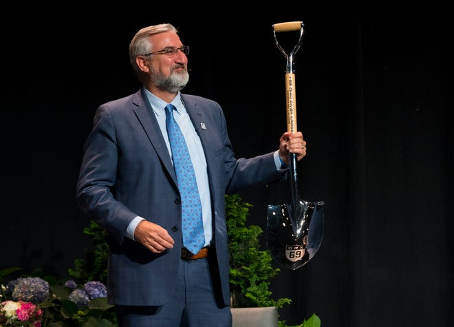 Indiana Governor Eric Holcomb holds up an Ohio River Crossing groundbreaking shovel gifted to him by Evansville Mayor Lloyd Winnecke after announcing $475 million in road projects including $200 million to finish up the last mile and a half of Interstate 69 from Evansville to the Kentucky border during the Evansville Regional Economic Partnership's Lunch Friday afternoon, June 11, 2021.