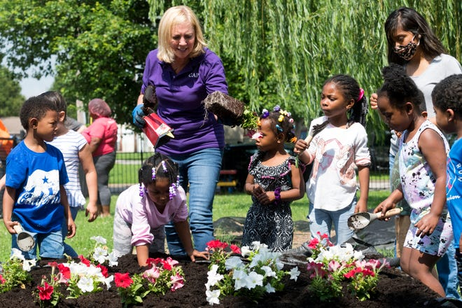 CAPE Head Start's Director of Children's Services Mary Goedde, center, assists kids as they learn to dig holes and plant flowers in their new raised garden beds Friday morning, June 11, 2021.