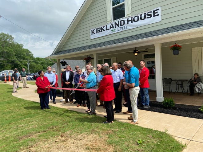 Carl and Alice Kirkland hold the scissors before cutting the ribbon in front of the Kirkland House at Aspell Recovery Center on June 10, 2021.