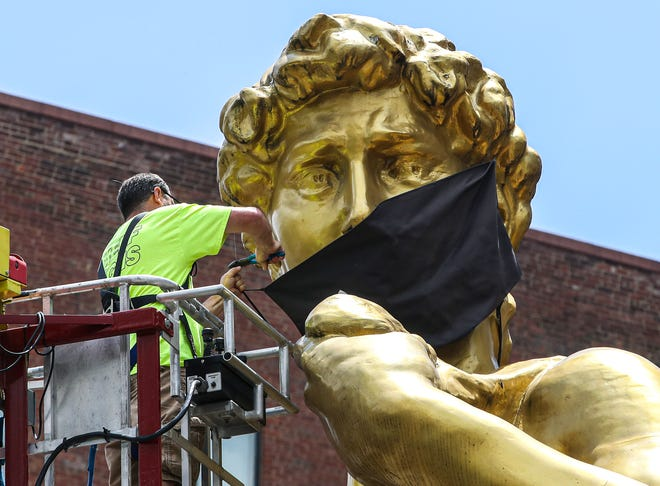 Robert Embry of Rueff Sign Co. removes the mask from the statue of David outside the 21C Museum Hotel on June 11, 2021, the day Gov. Andy Beshear formally lifted the mask mandate.