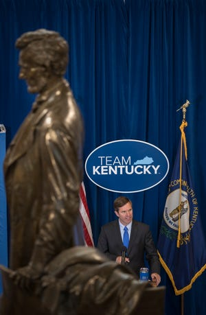 Kentucky Governor Andy Beshear in flanked by the statue of President Abraham Lincoln in the Capitol rotunda while giving his last Covid-19 update. June 11, 2021