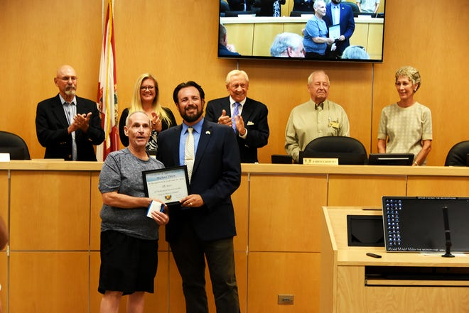 City Council chairman Jared Grifoni presents an award for 35 years of service to Mike Ehlen, left. The Marco Island City Council met June 7 in council chambers.