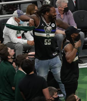 Green Bay Packers linebacker Za'Darius Smith (55) and running back Aaron Jones cheer on the Milwaukee Bucks during Game 3 of the Eastern Conference semifinals at Fiserv Forum.