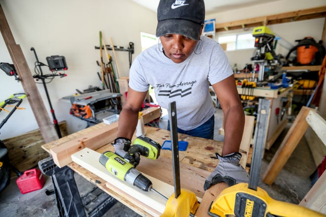 """She Slangs Wood owner Tonda Thompson works on the base of a pinewood dining table on Thursday, June 3, 2021, at her home in Milwaukee. She first uses wood glue and then drills in screws. If the screws fail, """"the glue will hold,"""" she said."""