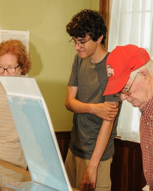 Ethan White (center) was on hand to discuss his discoveries as the Granville Historical Society Museum reopens to the public.