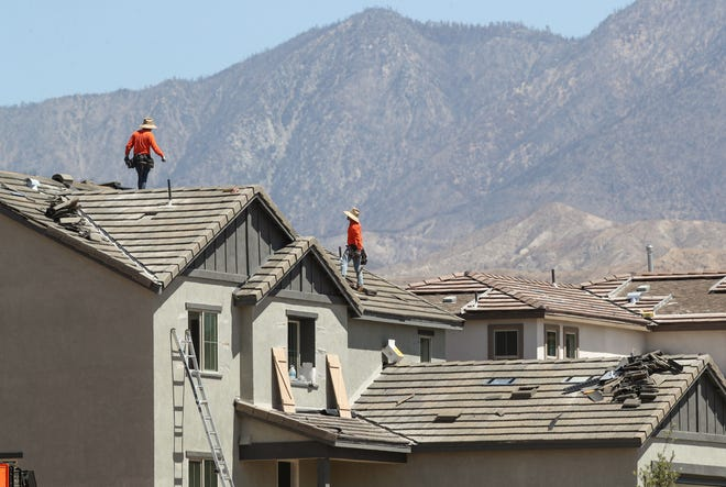 Construction workers build new homes in the Atwell development in Banning, June 11, 2021.