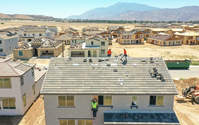 Construction workers build new homes in the Atwell development in Banning where about 4,500 new homes are in various stages of construction, June 11, 2021.