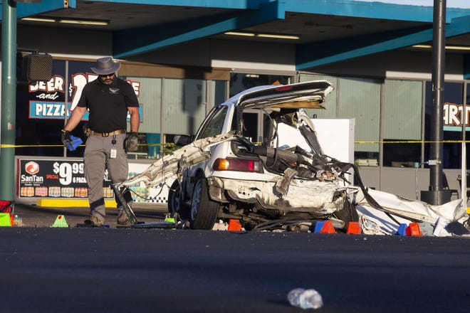 Police officers place markers at the scene of a deadly car crash involving at least two cars and a bus that left two people dead at the intersection of Seventh and Missouri avenues in Phoenix on June 10, 2021. (Benjamin Chambers/The Republic)