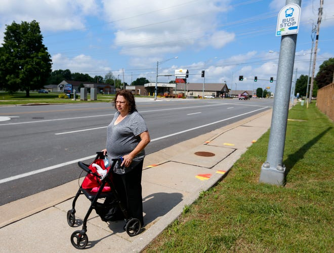 Elizabeth Rever waits for the bus along Republic Road after exercising at the Pat Jones YMCA on Friday, June 11, 2021