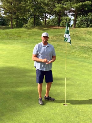 Steve Ashford stands next to the par-4 14th pin after recording a hole-in-one during the Coconis Furniture League on Tuesday at EagleSticks. Ashford, of Pataskala, and Zanesville's Zak Forker recorded aces on the hole in back to back groups.