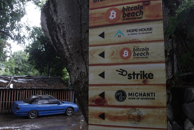 A sign that advertises the acceptance of cryptocurrencies at local businesses stands at one of the entrances of Zonte Beach in Tamanique, El Salvador, Wednesday, June 9, 2021.