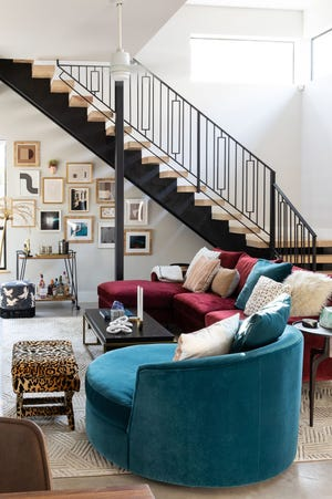 Bold furniture, pops of color in the artwork, and patterns in the pillows and footstool bring together this room designed by Maureen Stevens. She used the line of the staircase to create architectural elements underneath with framed photos.