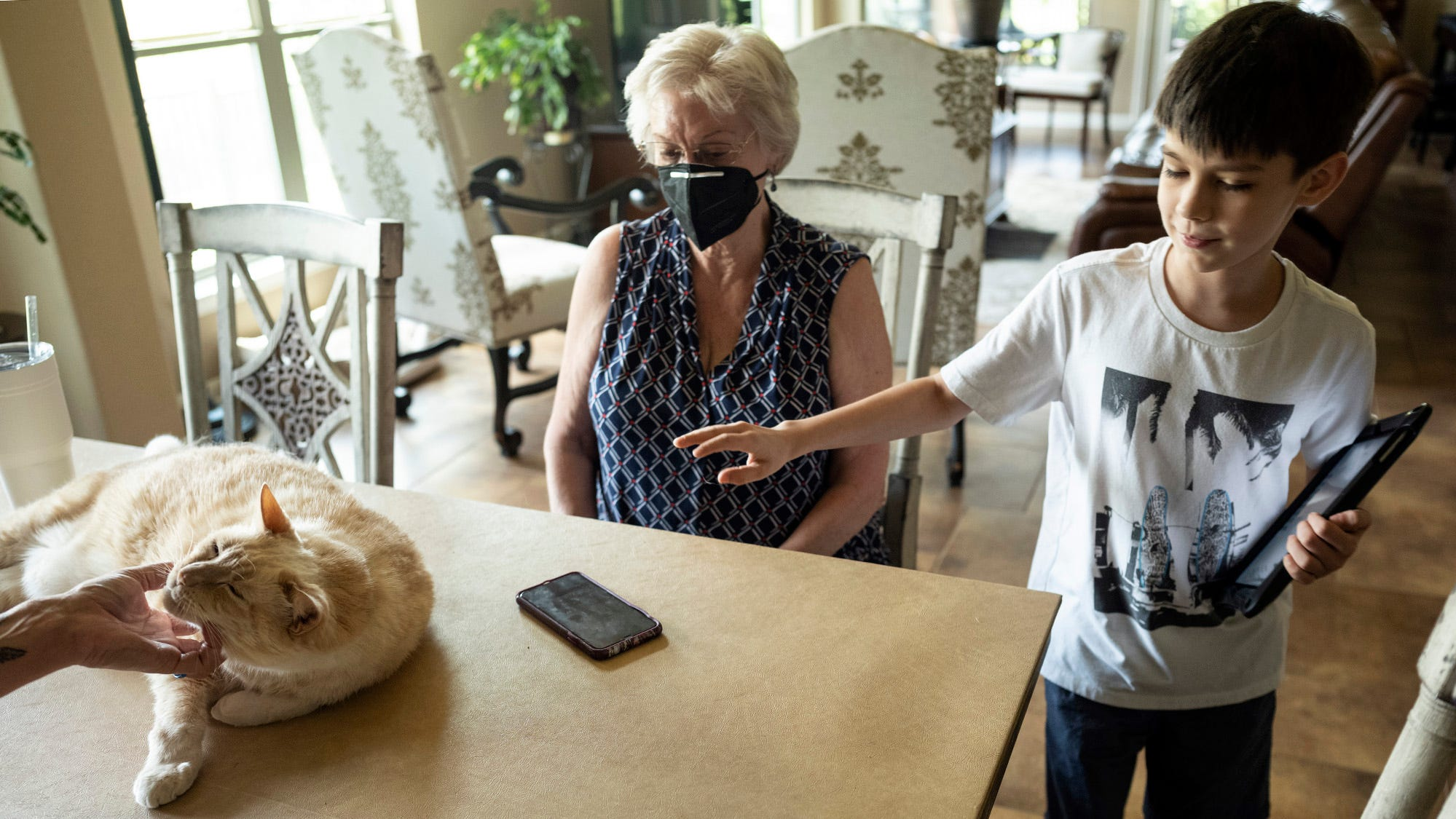 Carol Toman watches her grandson Raymond Gallardo change direction, from petting her cat, Hyperion, also petted by her mother, Sarah Gallardo, to playing on her iPad on Friday at Toman's in Round Rock.