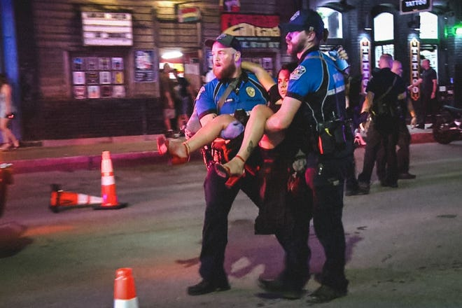Police carry away a woman injured in a mass shooting early June 12 in downtown Austin, Texas. At least 14 people were injured. (Photo taken from video.)