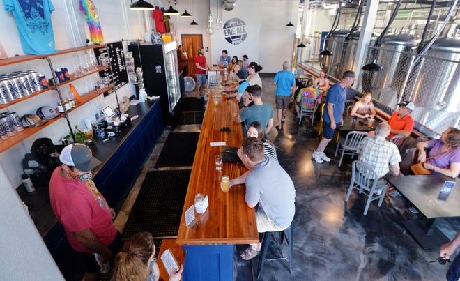 Guests sit inside the Erie Ale Works bar area during a grand opening on Saturday in Erie. Co-founders Steve Anthony and Jeff McCullor invested nearly $500,000 into the business in early 2020 but were unable to fully open due to the pandemic.