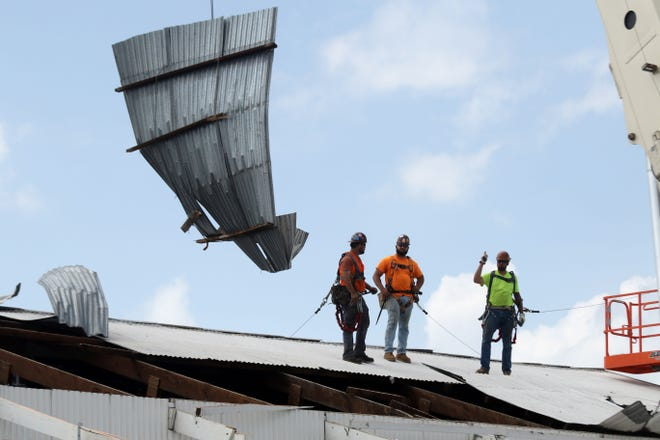 Workers with Seither and Cherry Co., contractors from Keokuk, remove the damaged roofing from the shed of Huffman's Farm and Home Saturday at 201 E. Agency Road in West Burlington.